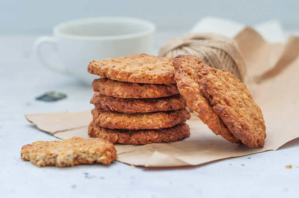 Healthy anzac biscuits stacked on brown paper