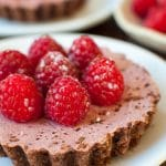 Rich luscious raspberries accompanying a decadent raspberry chocolate tartlet.