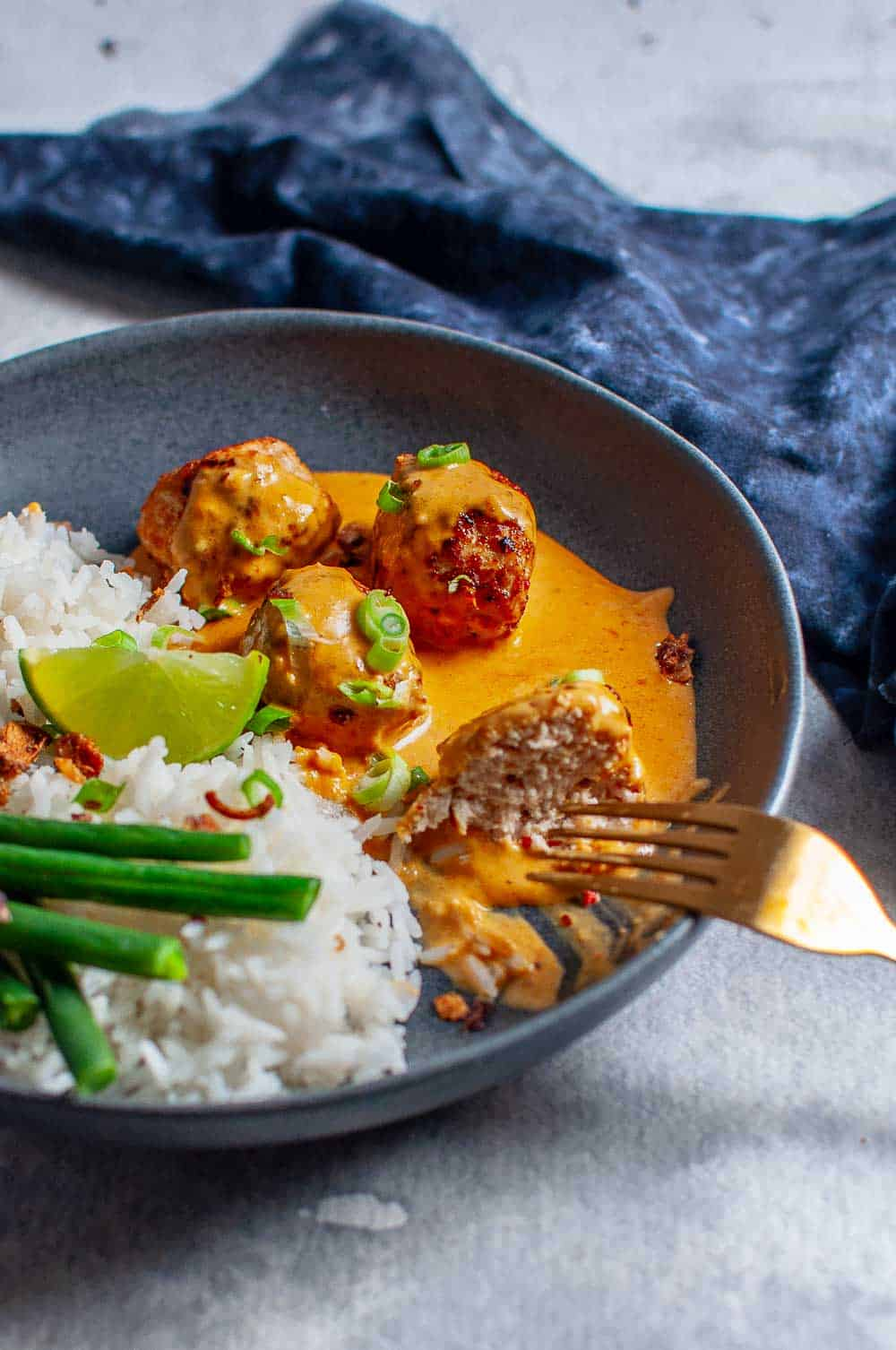 Thai Chicken Meatballs With Peanut Sauce and rice being eaten with a fork