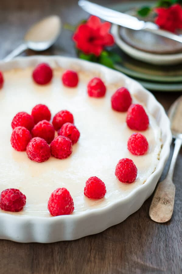 crustless cheesecake in a white dish with raspberries on top