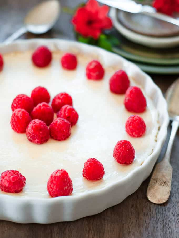 crustless cheesecake in a white dish with raspberries