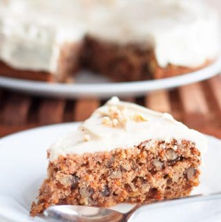 A single slice of carrot cake on a white plate