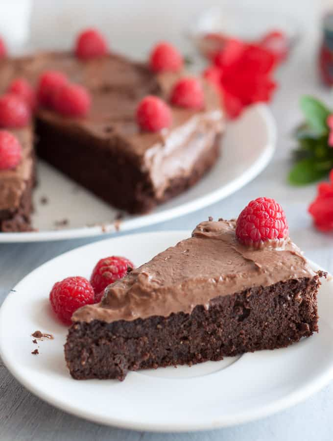Gluten free mud cake on white plate with raspberries