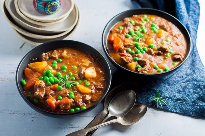 two bowls of pressure cooker lamb stew with spoons