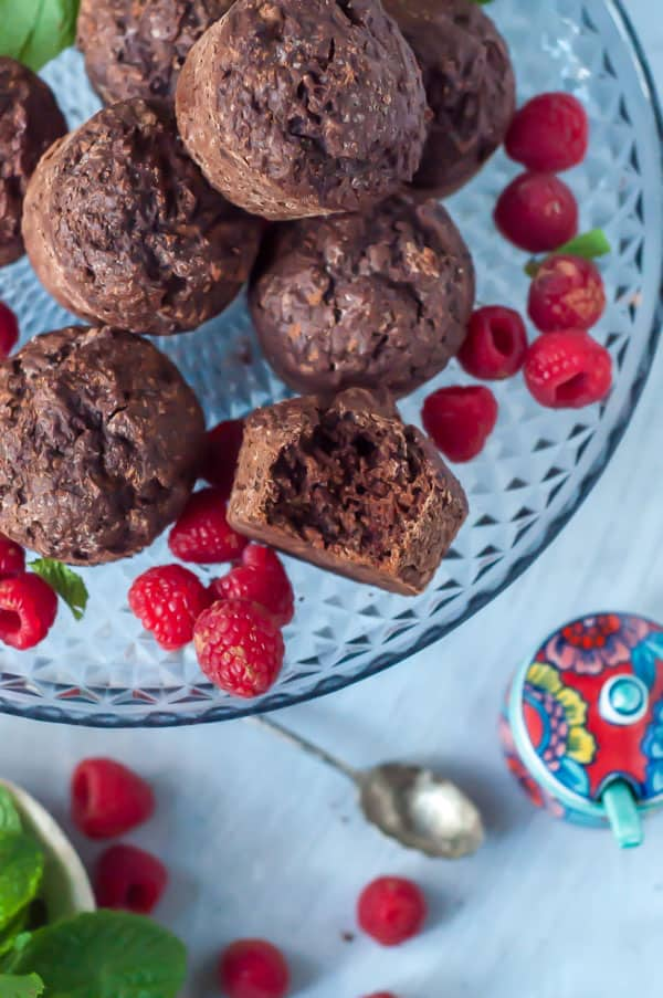 6 chocolate Sweet Potato Muffins on a platter with raspberries