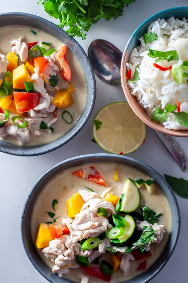 two bowls of thai green chicken curry with rice and lime