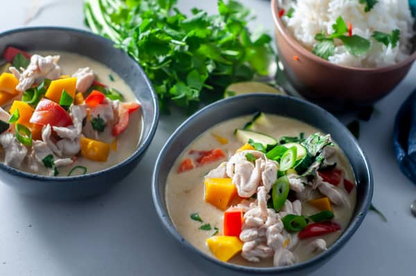 a bowl of thai green curry on a bench ready to eat