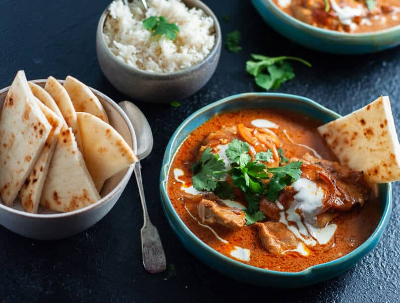 A bow of pressure cooker butter chicken with nan bread