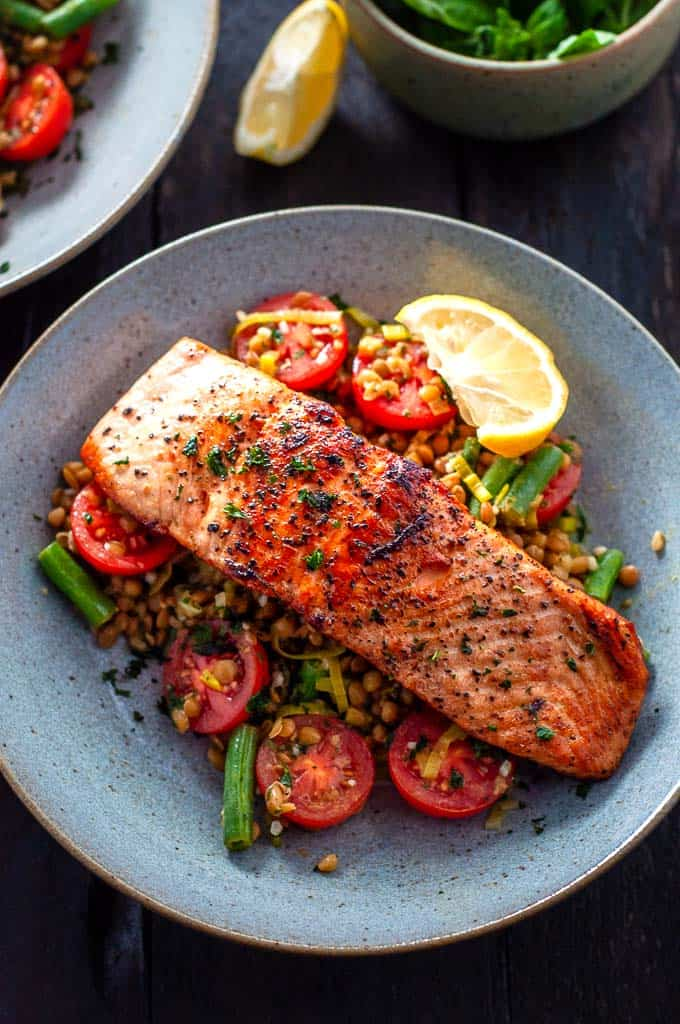 Salmon with leeks, tomatoes, lentils and beans in a bowl