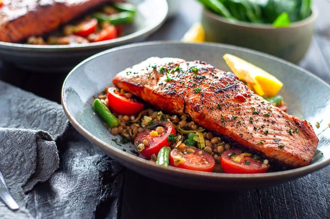 Pan fried salmon in a bowl with tomatoes and beans