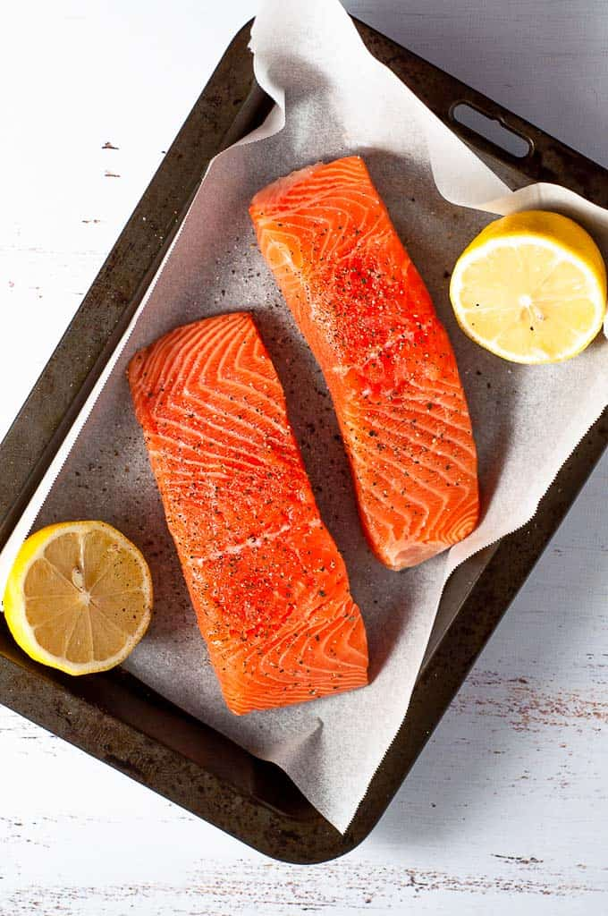 A tray with two fillets of salmon with lemon