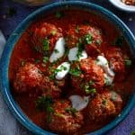 A bowl of slow cooked moroccan meatballs drizzled with sour cream and corriander