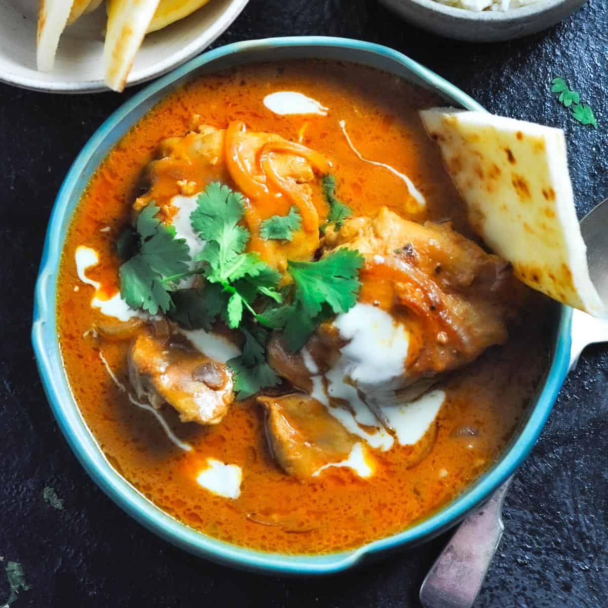 butter chicken curry in a bowl with roti