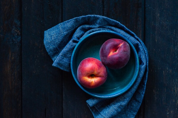 Two peaches in a blue bowl