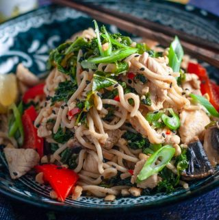 a bowl of chicken and kale stirfry with chopsticks