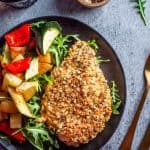 Quinoa Crusted Chicken in a black plate with roast vegetables