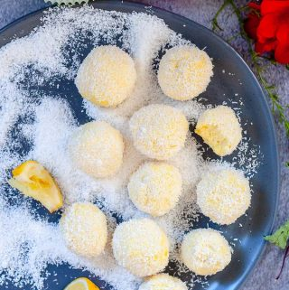Lemon bliss balls on a grey plate with coconut