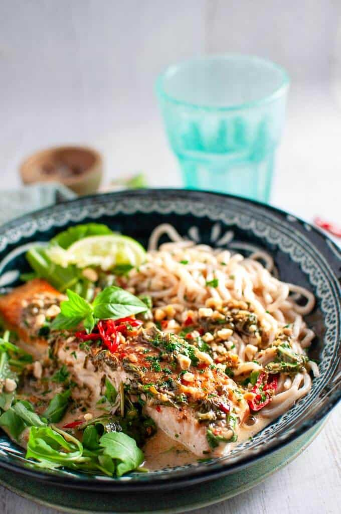 coconut lime salmon with noodles in a bowl, chilli and thai basil on top