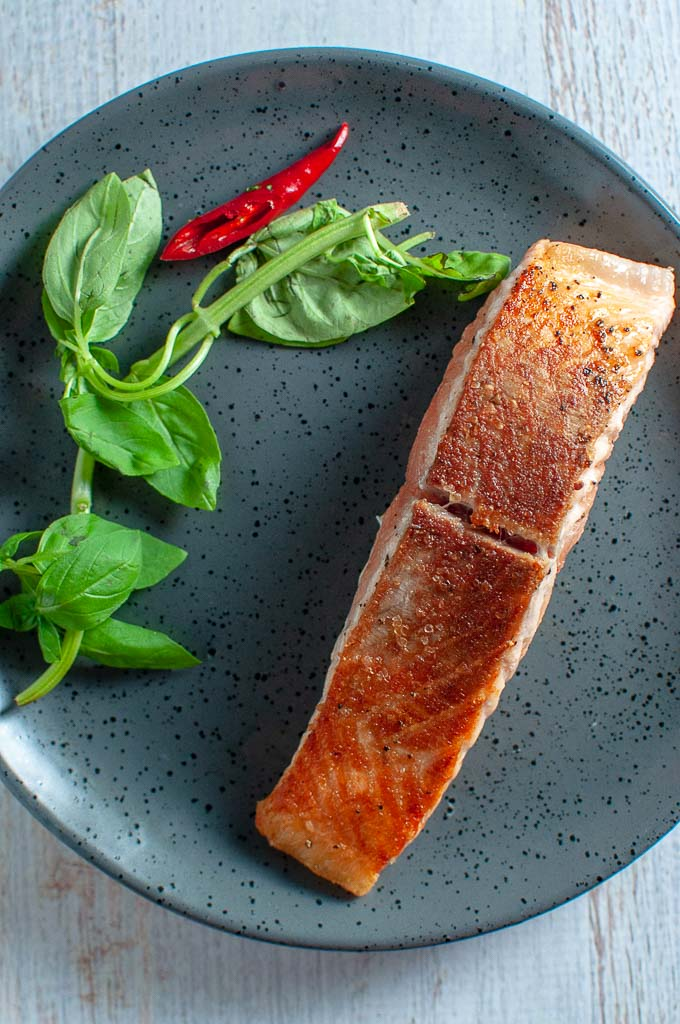 a piece of pan fried salmon on a grey plate