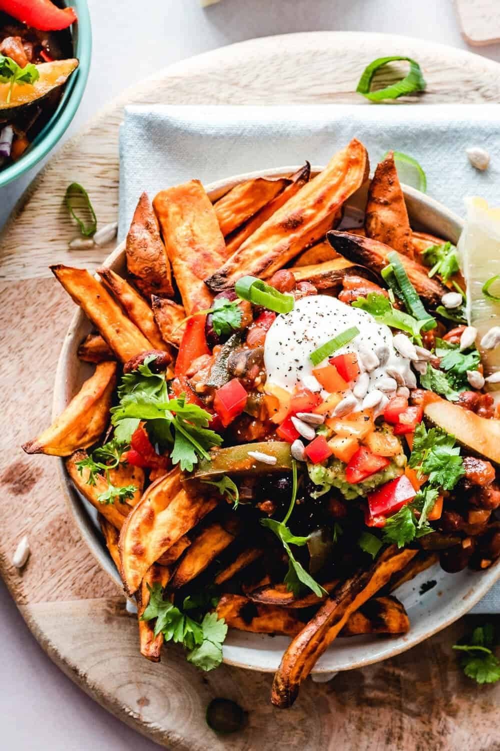 A plate sweet potato fries with sour cream and salsa