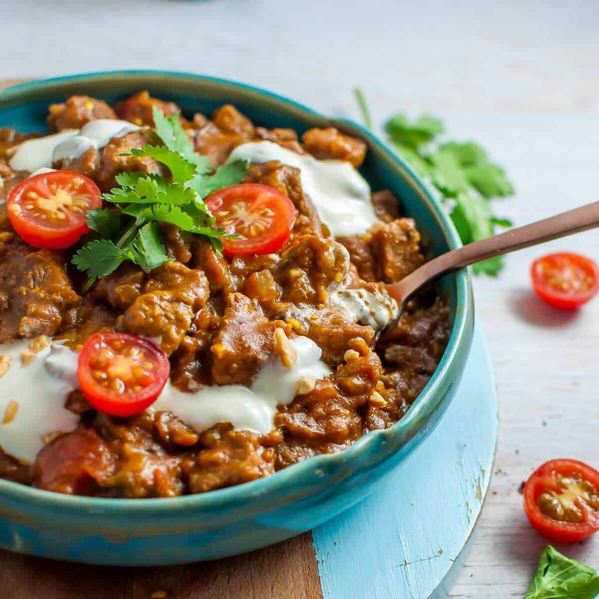 beef masala in a blue bowl with yoghurt and tomatoes