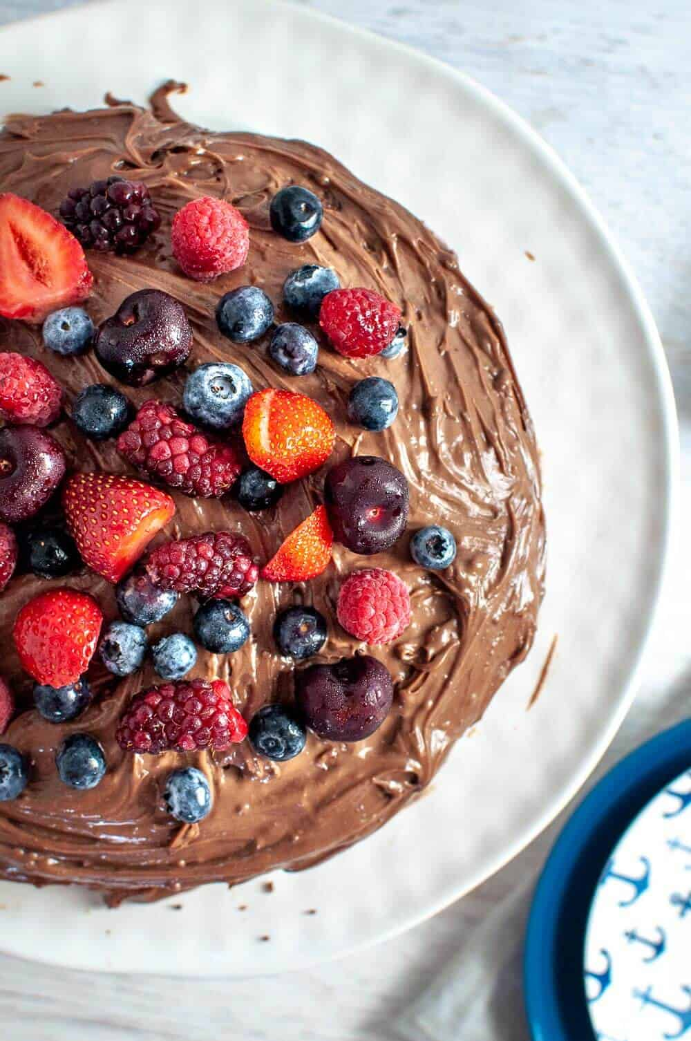 Chocolate date cake with ganache and berries on a white plate