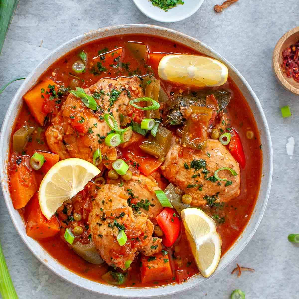 Chicken afritada stew in a bowl with lemon