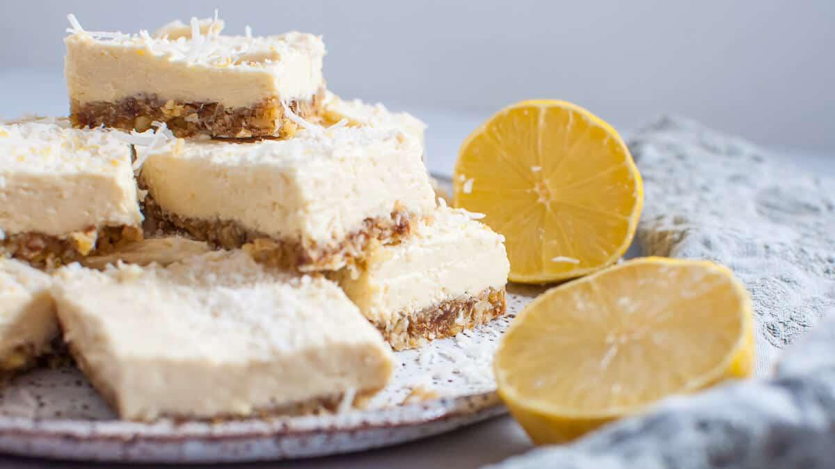 lemon coconut slice stacked on white plate