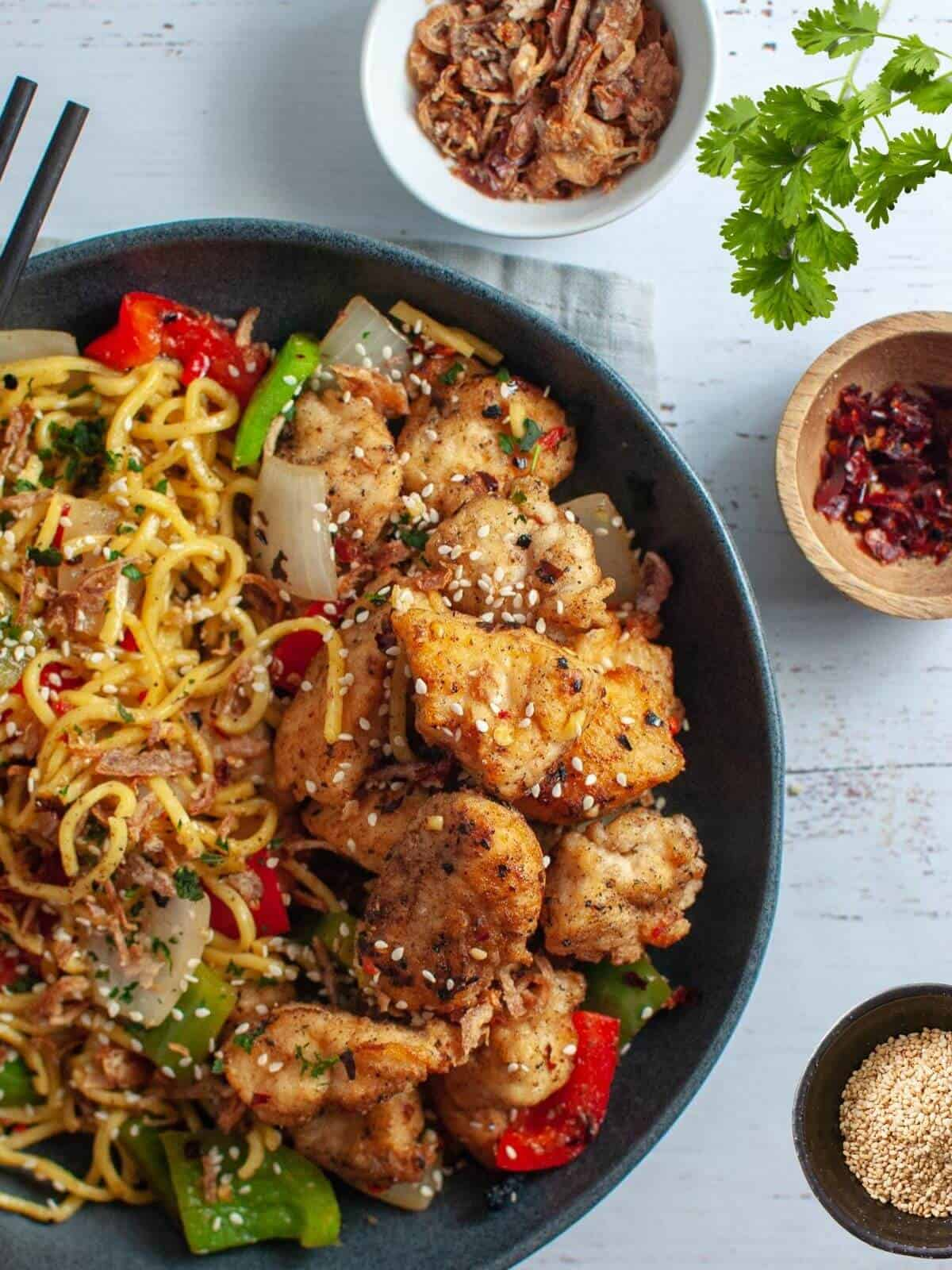 salt and chilli chicken with noodles in a bowl