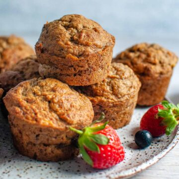5 banana muffins stacked on a serving plate