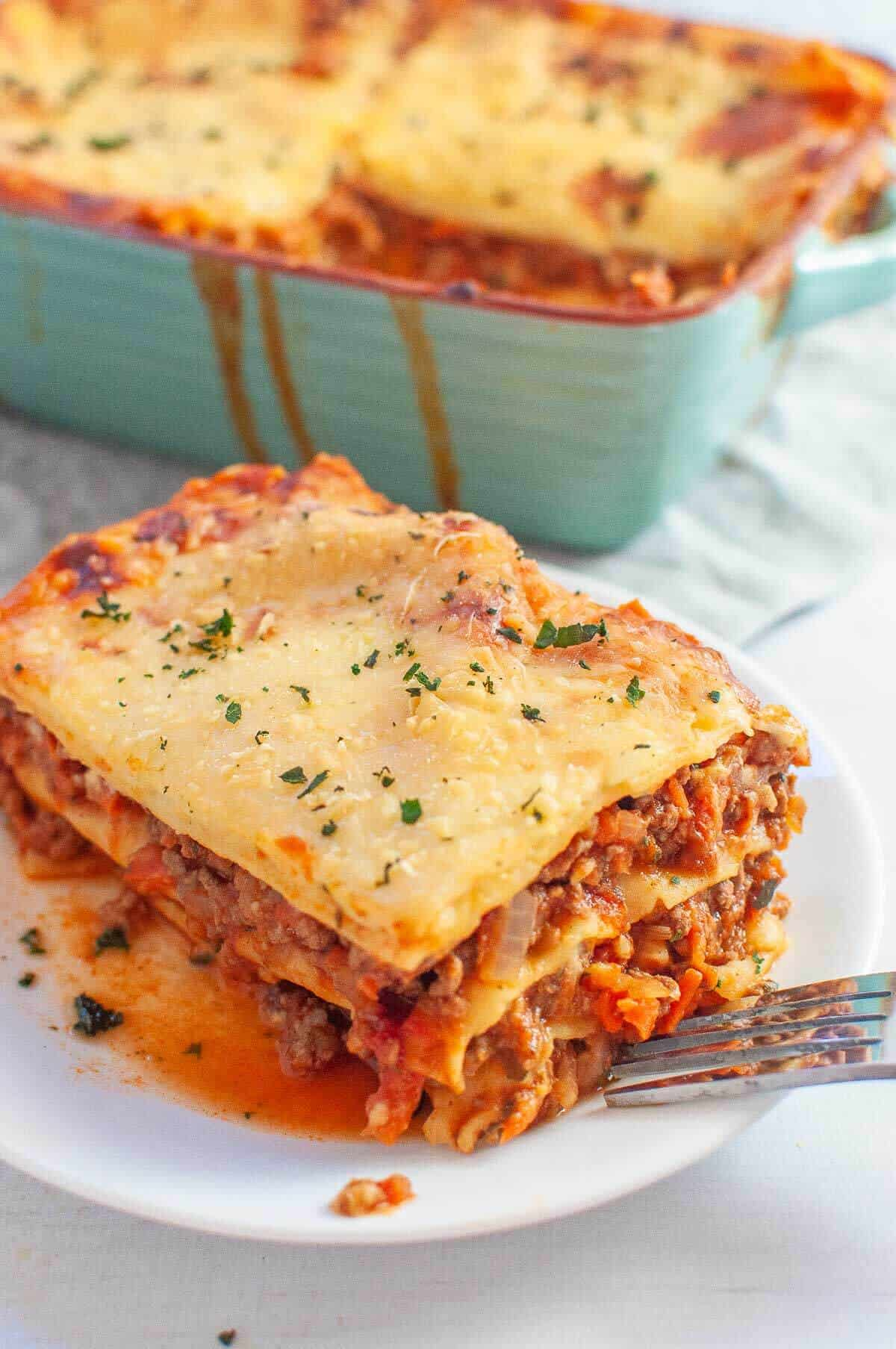 a serve of lasagna without ricotta on a white plate with a fork