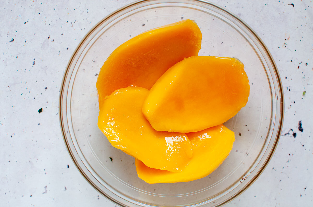 4 mango cheeks in a glass bowl