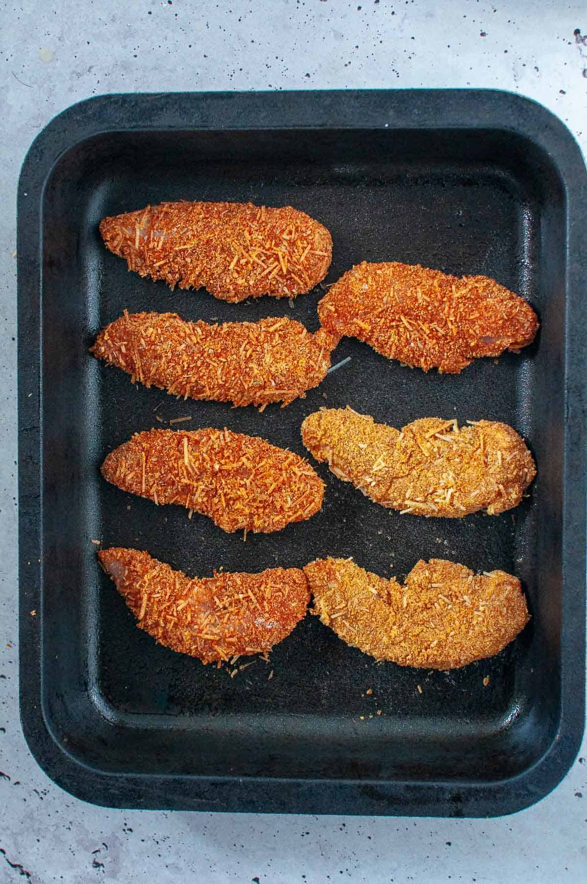 chicken tenders in a baking tray ready for oven