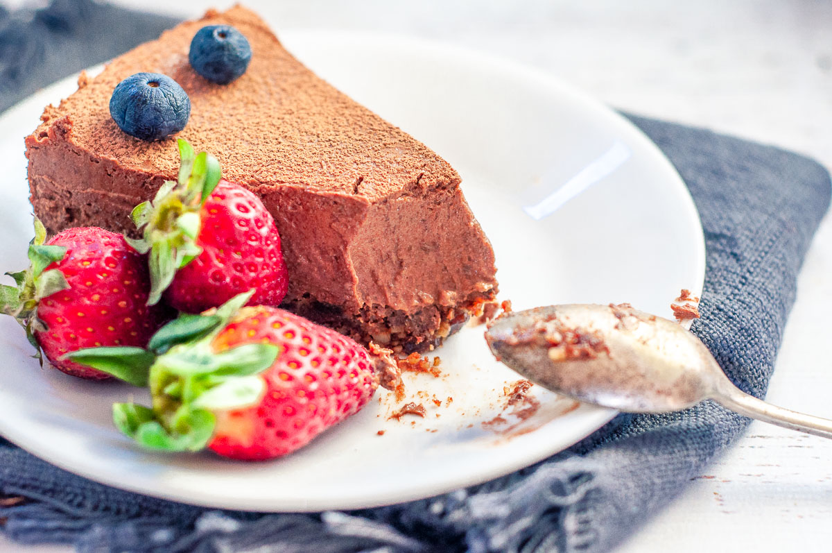a single slice of cheesecake on a plate with berries