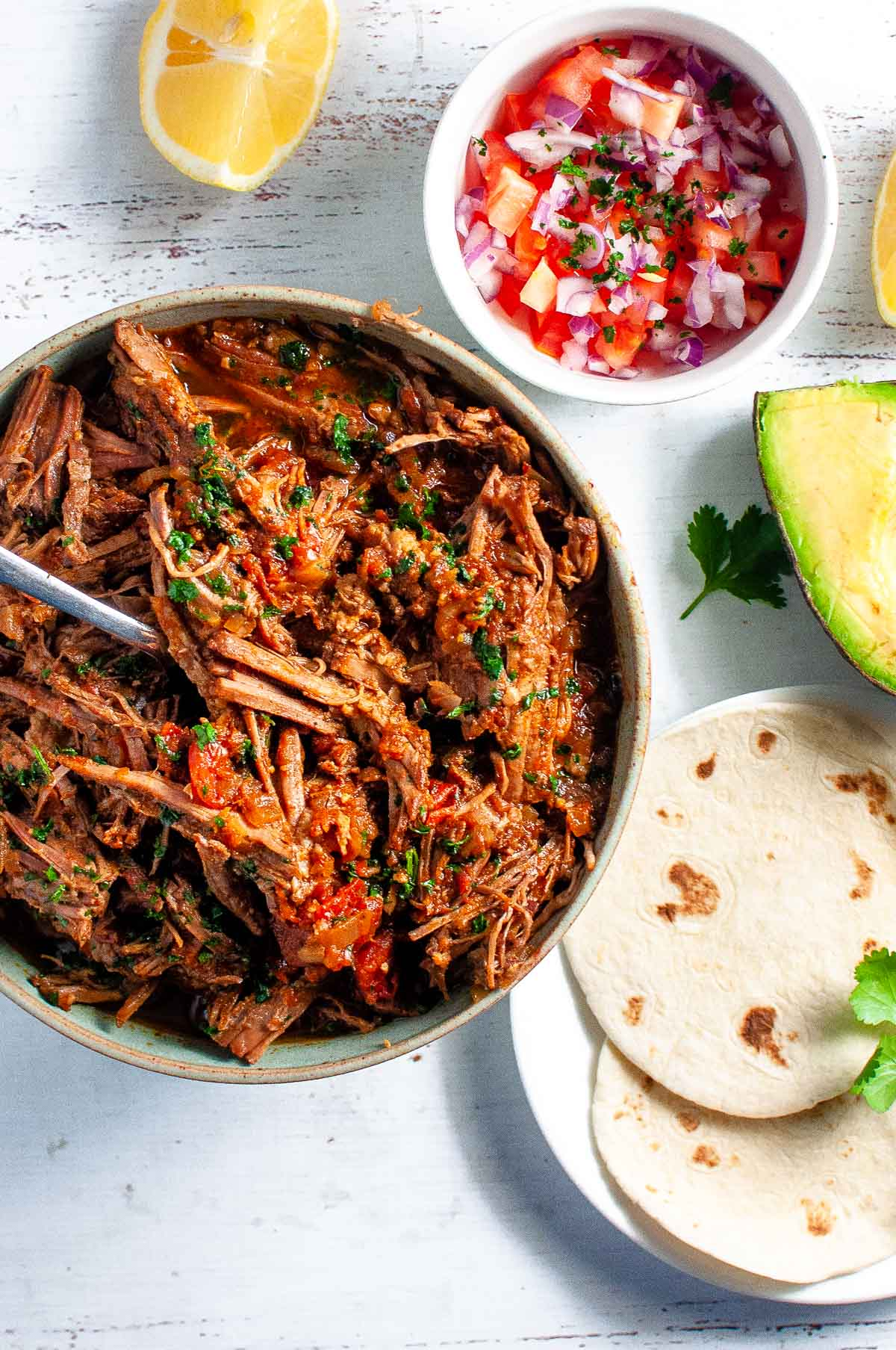 a bowl of shredded beef with soft tacos, salsa and avacado