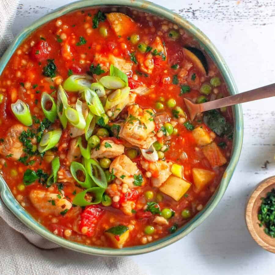 a bowl of spanish fish stew with a fork in