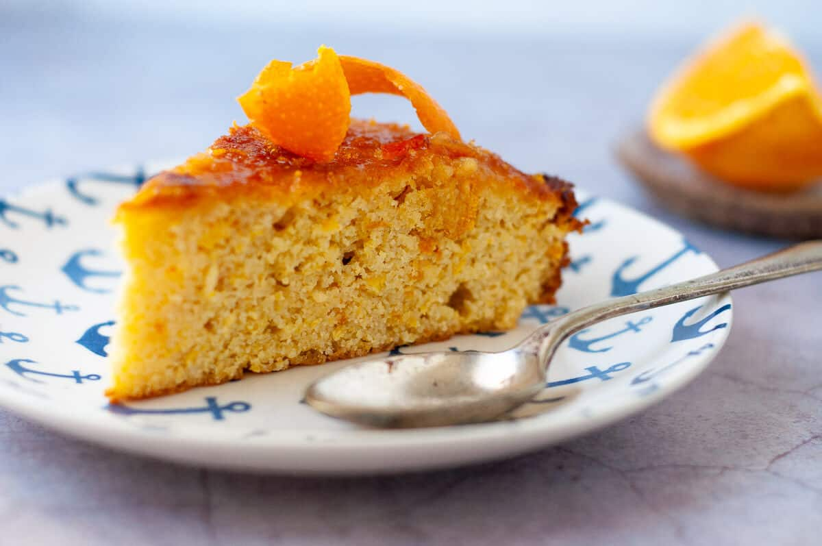 a slice of orange cake on a plate with spoon