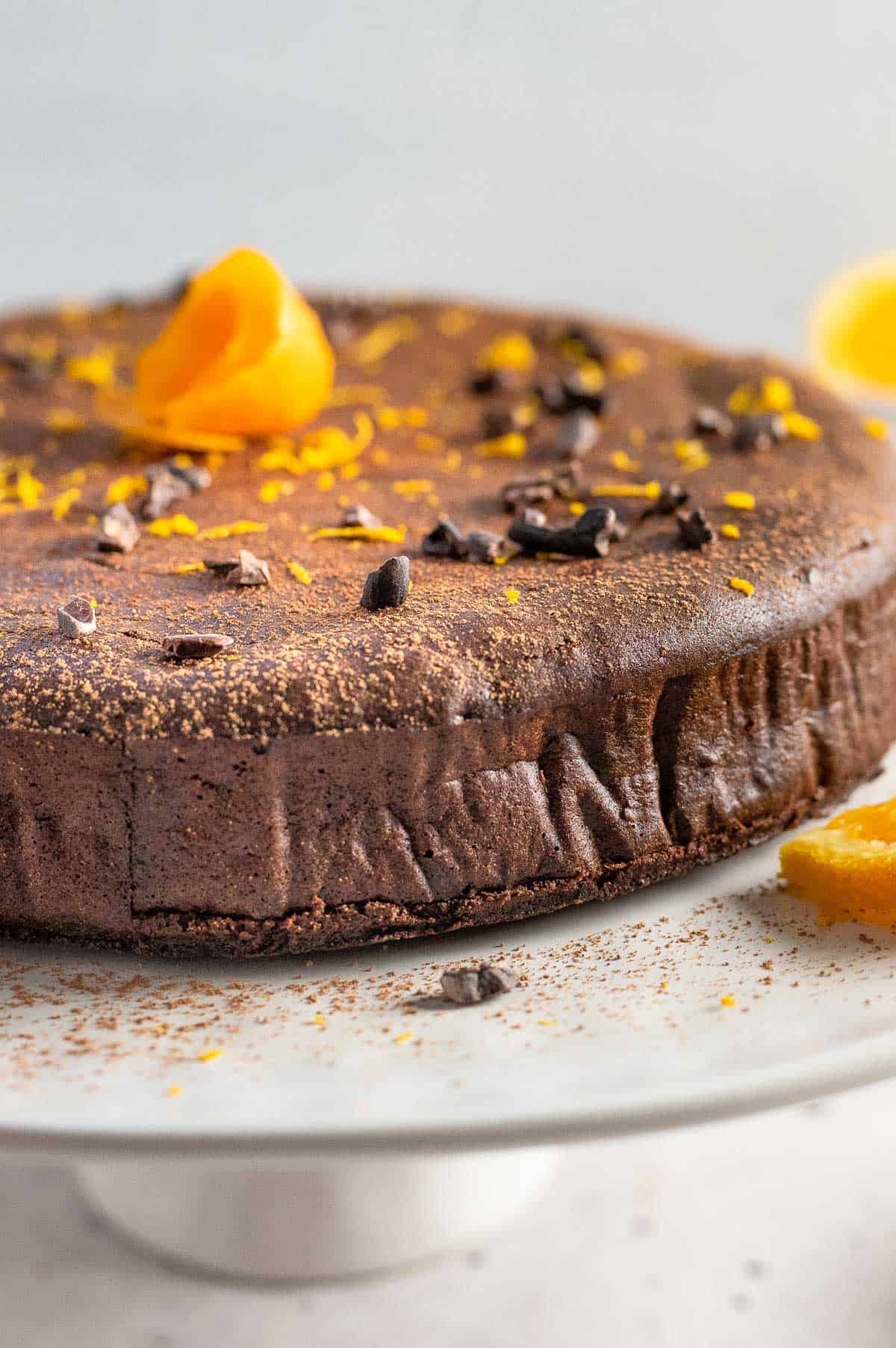 full chocolate orange cake on a cake stand