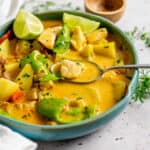 Yellow fish curry in a bowl with spoon
