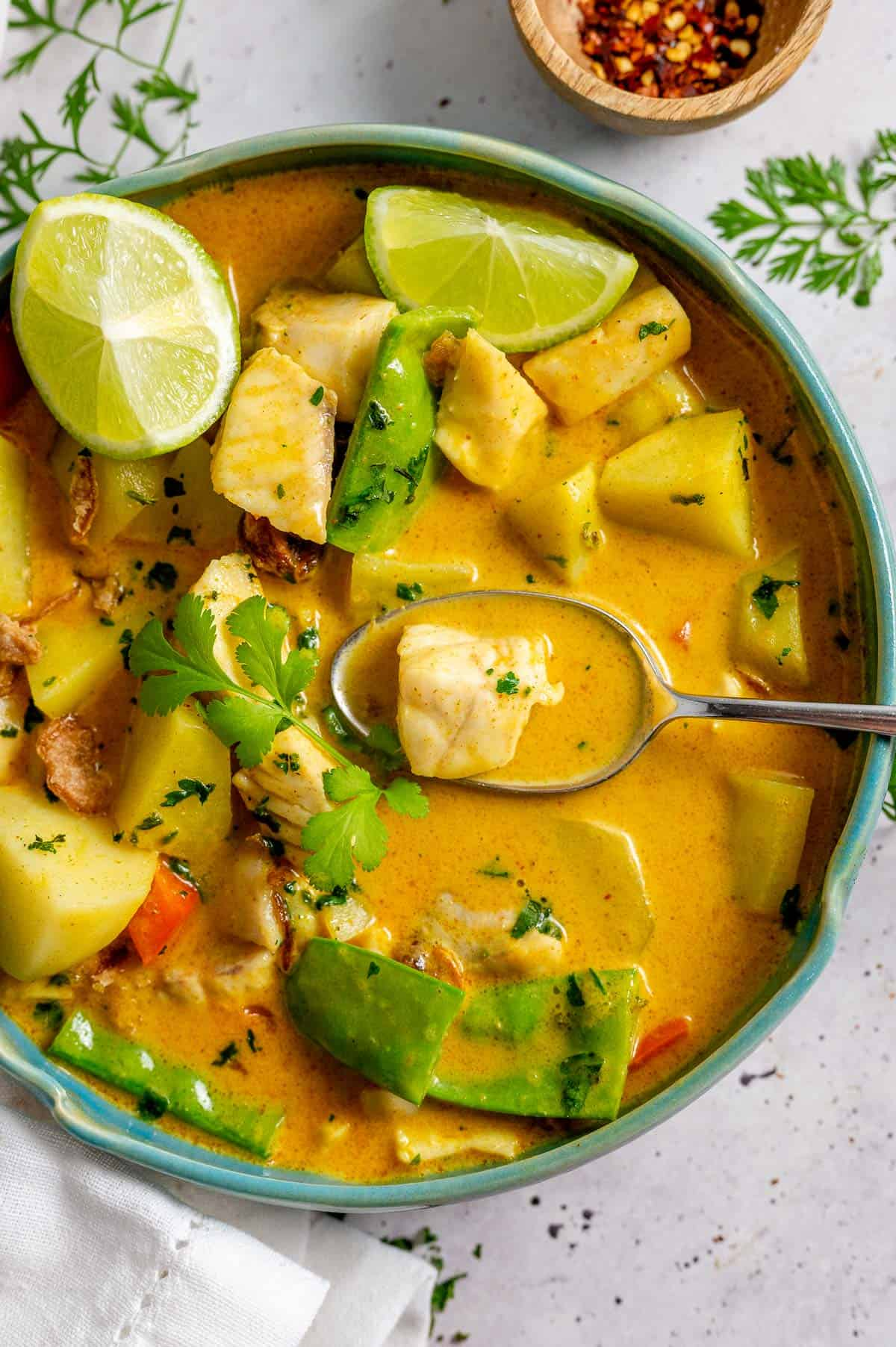 Yellow Fih curry in a blue bowl with a spoon and lime wedges