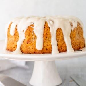 Coconut yoghurt cake with glaze on a cake plate