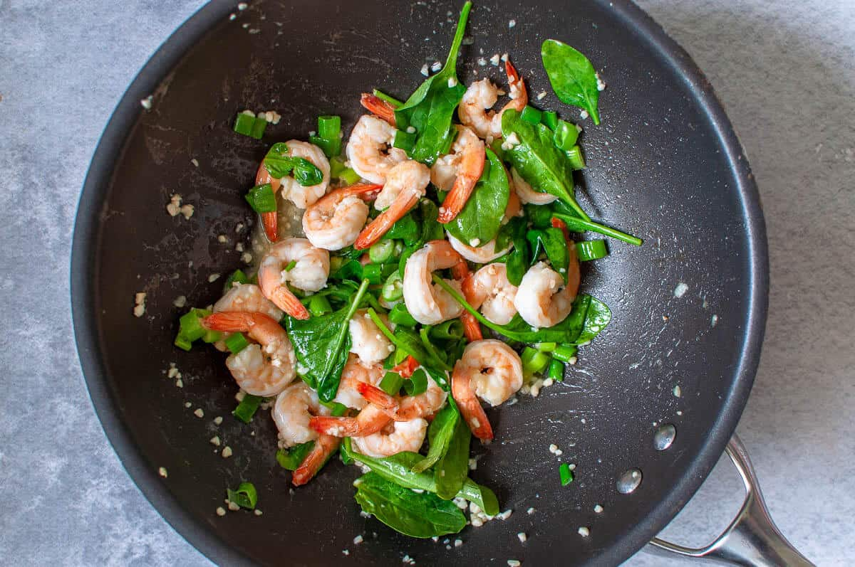 garlic prawns with shallots and spinach in a pan