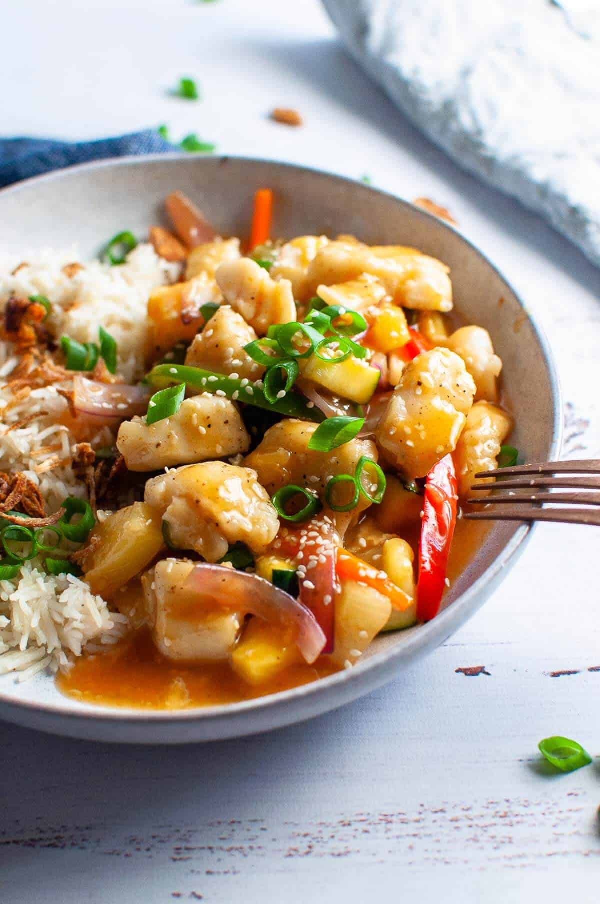 sweet and sour fish with rice in a bowl with fork ready to eat
