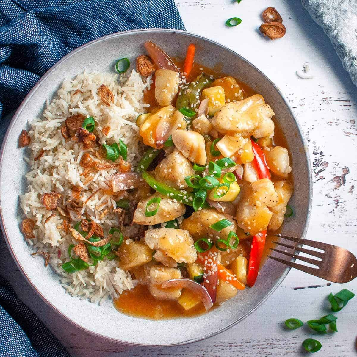 sweet and sour fish with rice in a bowl
