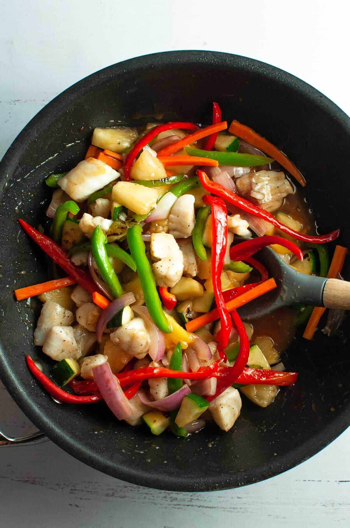 sweet and sour fish in the wok with vegetables