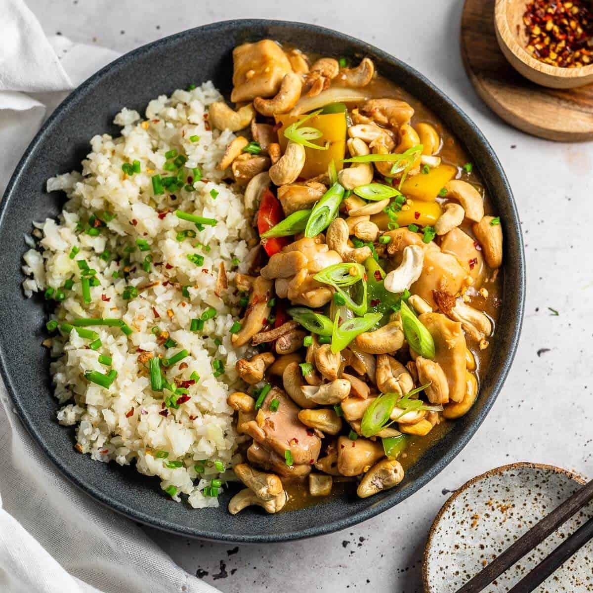 cashew nut chicken in a grey bowl with chopsticks