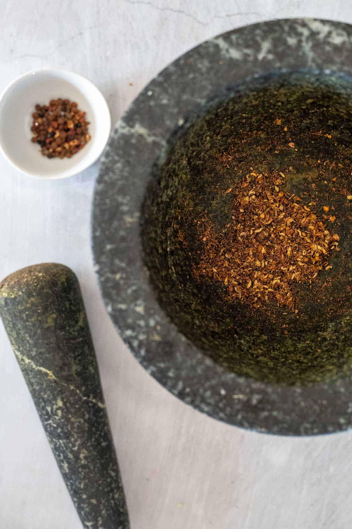 Grinding szechuan peppercorns in a mortar and pestle