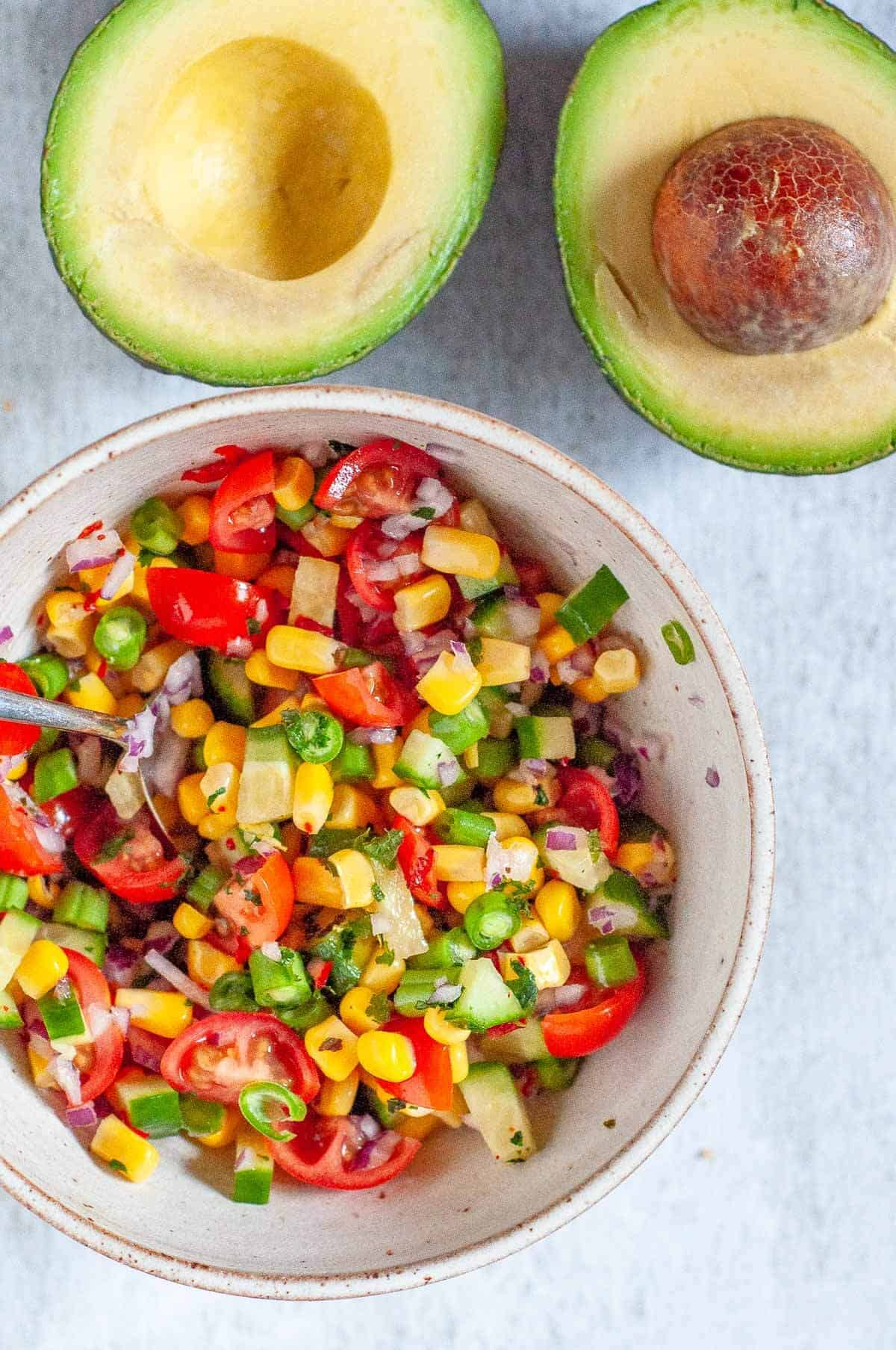 avocado halved and a bowl of chopped mexican salsa