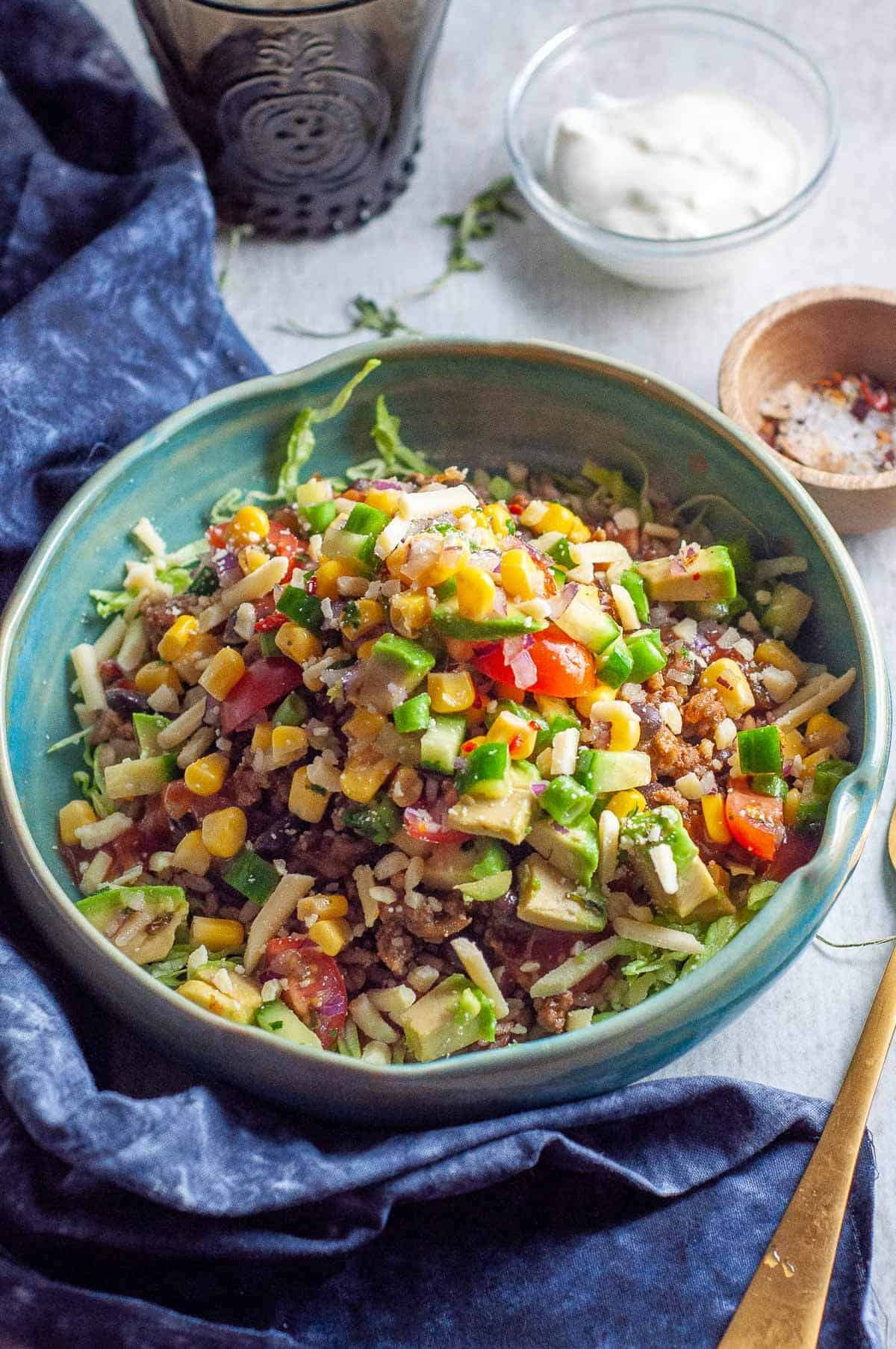 healthy burrito bowl with sour cream and avocado ready to eat