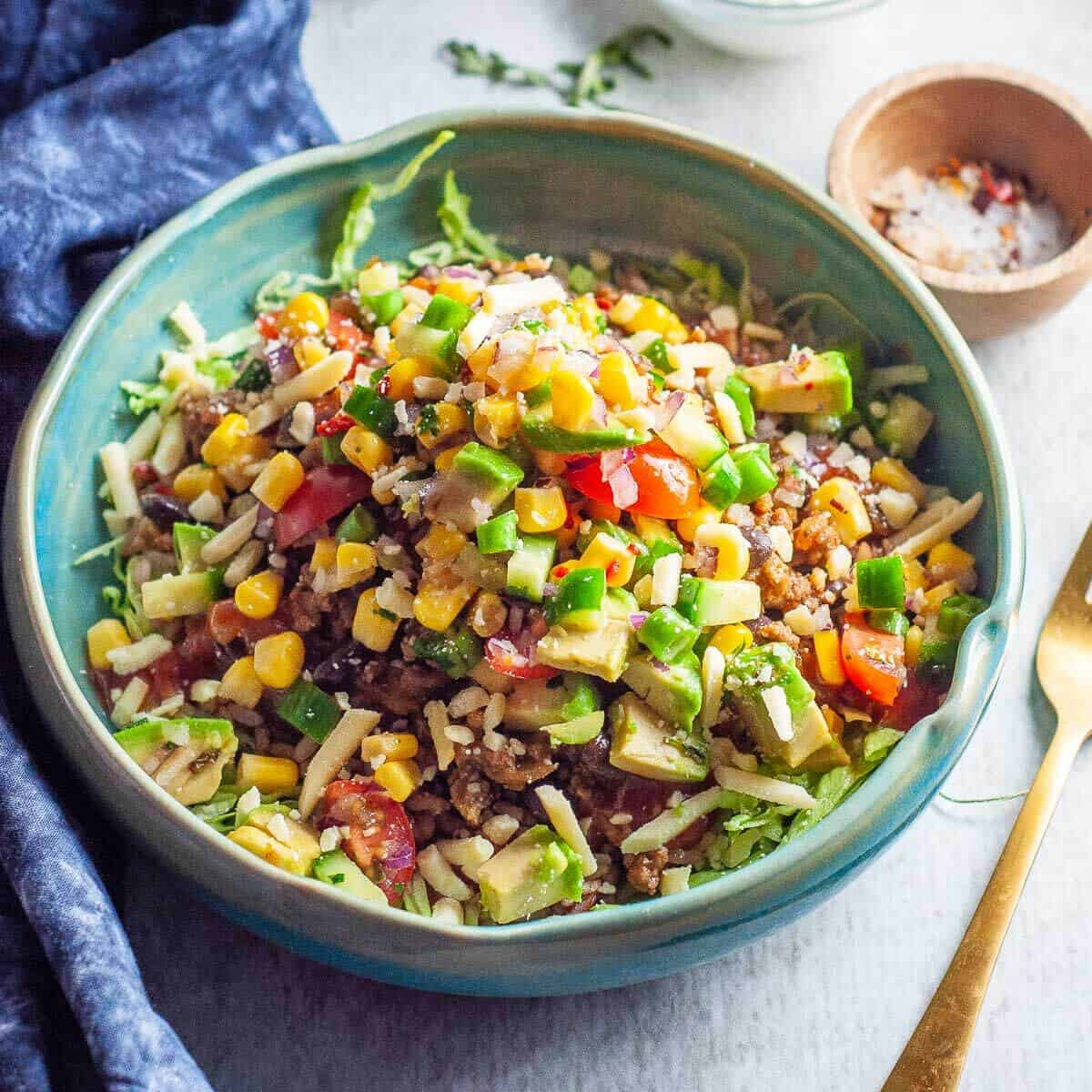 a green bowl with mexican beef and salsa piled high ready to eat